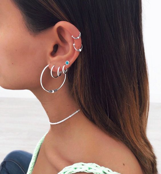 a boho look with stacked helix and stacked lobe piercings all done with bold and cool hoop earrings