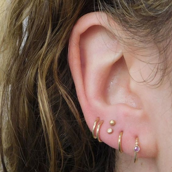 a bold and cool stacked lobe piercing with hoops and tiny studs is a fresh and cool idea to stand out from the crowd