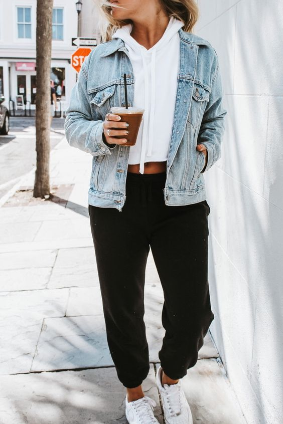 a casual look with a white cropped hoodie, black sweatpants, a blue denim jacket and white trainers