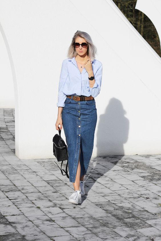 a casual outfit with a light blue shirt, a blue button up denim midi, white sneakers and a small black backpack