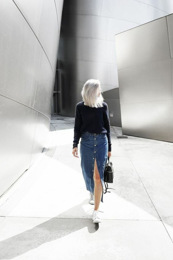 a casual outfit with a navy sweater, a blue denim button up midi, white sneakers and a black backpack