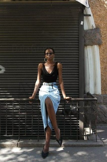 a chic look with a black draped top with bows on the shoulders, a bleached denim midi skirt, black mules and statement earrings