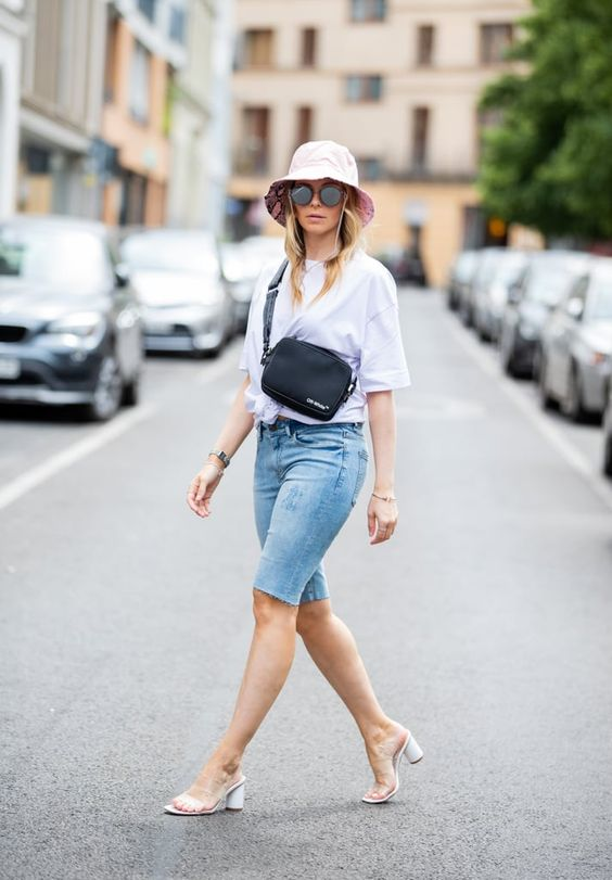 a chic outfit with a white tied up tee, blue denim biker shorts, a bucket hat, a black bag and sheer heels