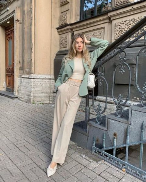 a chic summer to fall outfit with a neutral crop top, neutral trousers, a green oversized blazer and a white bag