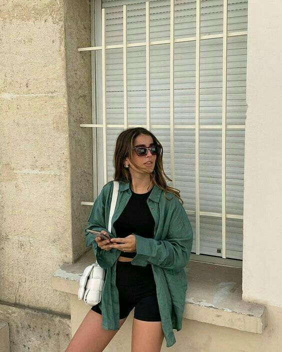 a comfortable everyday look with a black halter neckline crop top, black biker shorts, an oversized green shirt, a white woven bag