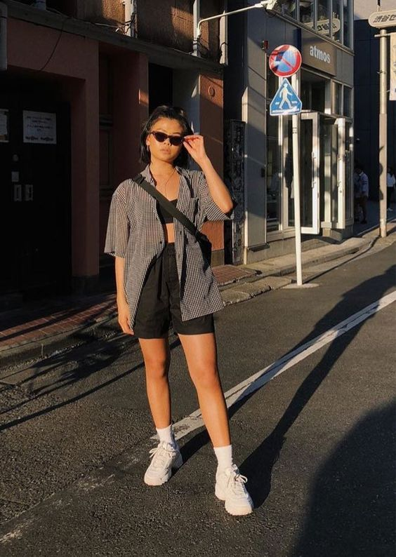 a comfy outfit with a crop top, linen shorts, a grey printed shirt, white socks and trainers plus a black bag