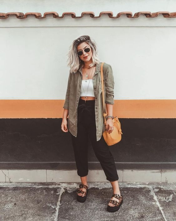 a comfy outfit with a white crop top, black linen pants, platform shoes, a grey chambray shirt and an orange bag for summer