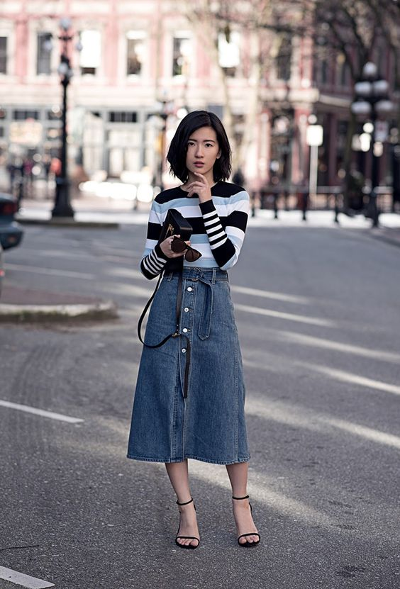 a contrasting striped jumper, a blue denim button up midi, black heels and a black bag for a chic look