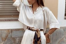 a cool satin two-piece set with a wide crop top and short sleeves, high waisted shorts with pockets, a colorful sash and a basket bag
