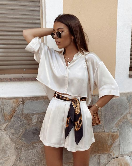 a cool satin two piece set with a wide crop top and short sleeves, high waisted shorts with pockets, a colorful sash and a basket bag