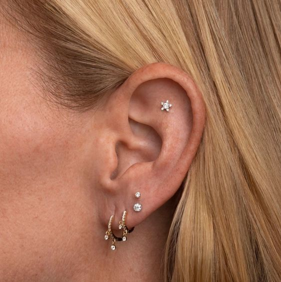 a cool stacked lobe piercing with gold hoops and studs plus a single flat piercing with a star stud for a dreamer