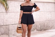a cool vacation two piece set with an off the shoulder top and high waisted shorts, black sandals and a woven bag