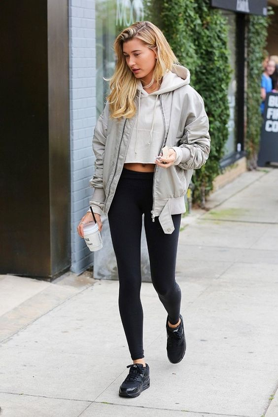 a creamy cropped hoodie, a grey bomber jacket, black leggings, black trainers for a comfy everyday look