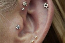 a delicate look with stacked lobe, helix and forward helix piercings plus a tragus one and cool floral and usual studs