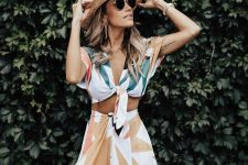 a dreamy vacation look with a printed botanical tied up crop top and a matching high waisted maxi skirt plus a straw hat
