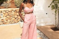 a fab pink linen set with a bra top and wideleg pants, a white bag and pink statement earrings for a gorgeous vacation look