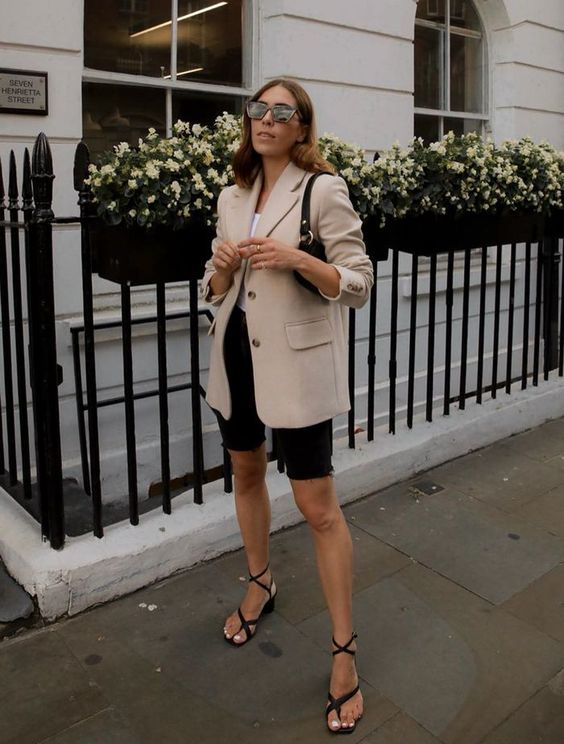 a fashionable office look with a white top, black denim shorts, a tan oversized blazer, black lace up heels and a black bag