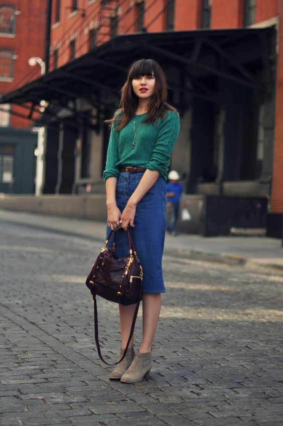 a green jumper, a blue denim button up midi, grey booties, a brown belt and a purple bag for a bold jewel tone look