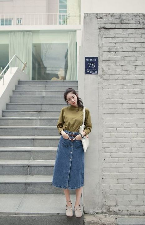 a green turtleneck, a blue button up denim midi, grey shoes and a white tote for an everyday fall look