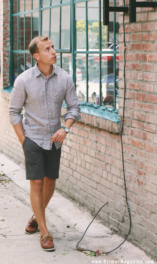 a grey linen shirt, graphite grey shorts and brown boat shoes for a comfortable summer look