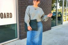 a grey sweatshirt, a blue denim midi skirt, silver shoes and a black clutch for a stylish and trendy outfit
