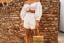 a jaw-dropping vacation outfit with a white off the shoulder puff sleeve top and high waisted shorts, strappy metallic shoes and a gold bag