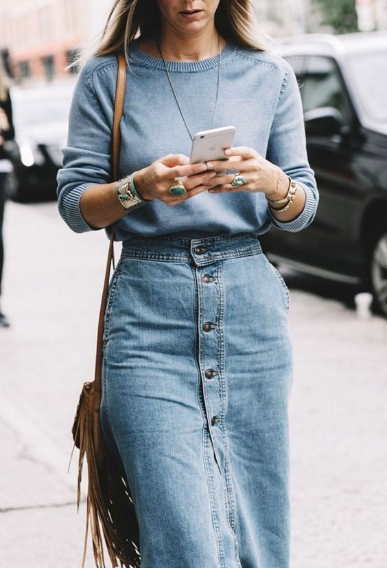 a light blue jumper, a denim button up midi skirt with pockets, a tan fringe crossbody bag and statement accessories