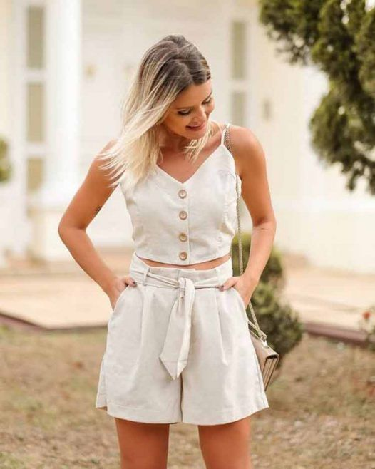 a lovely and cool linen two piece set with a button up crop top, high wasited shorts with porckers and a neutral bag are ideal for summer