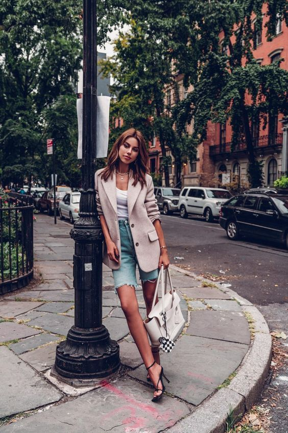 a lovely look with a white top, a neutral linen blazer, blue denim biker shorts, black strappy heels and a white tote