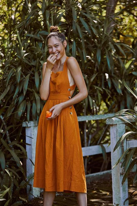 a lovely orange linen midi sundress with buttons on the side and an open back, thick straps and a square neckline