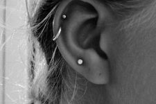 a minimalist look with a single lobe piercing plus a double helix one done with studs and a hoop earring is lovely