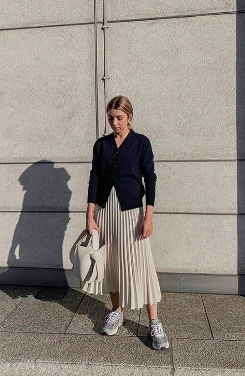 a navy cardigan, a creamy pleated midi, grey trainers, a creamy bucket bag for a chic and feminine look