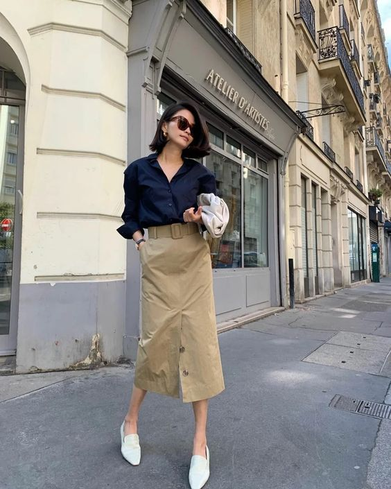 a navy shirt, a beige midi skirt with buttons and a belt, white loafers and a white bag for a cool look
