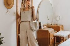 a neutral linen outfit with an A-line crop top, wideleg pants, brown slippers and a linen bag for a hot day