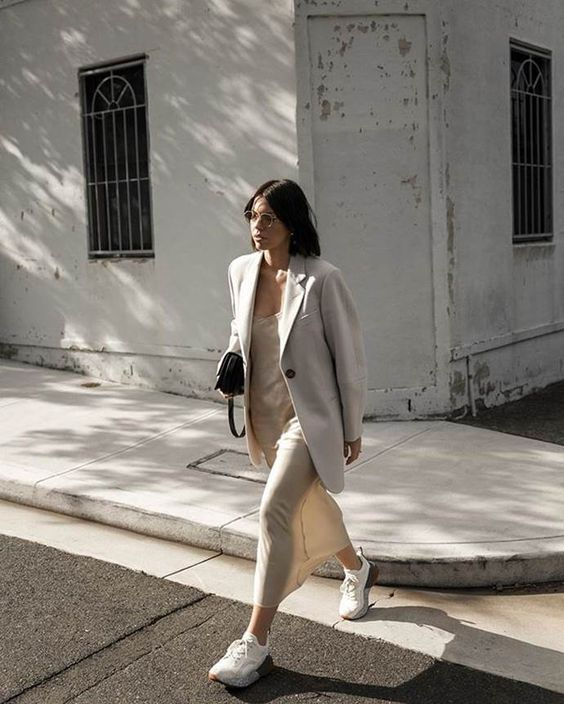 a neutral slip maxi dress, a creamy oversized blazer, white trainers and a black bag for a minimalist look