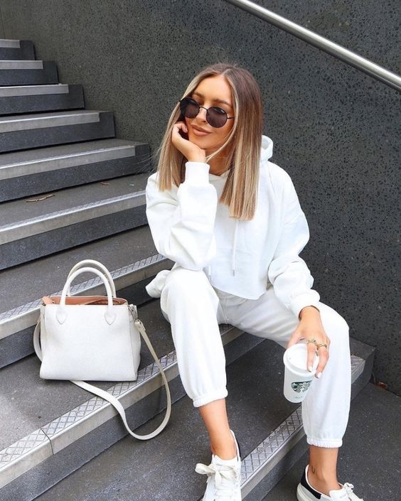 a perfect white outfit with a cropped hoodie, sweatpants, trainers and a bag is amazing