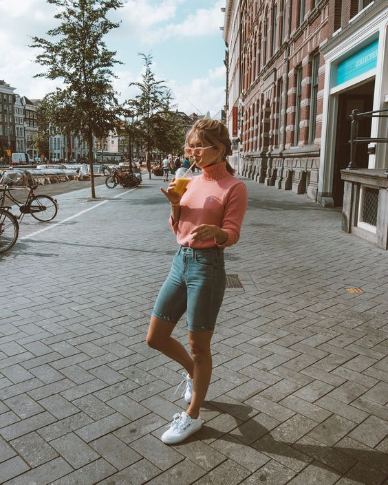 a pink turtleneck, blue denim biker shorts, white sneakers, pink sunglasses for a cold summer day