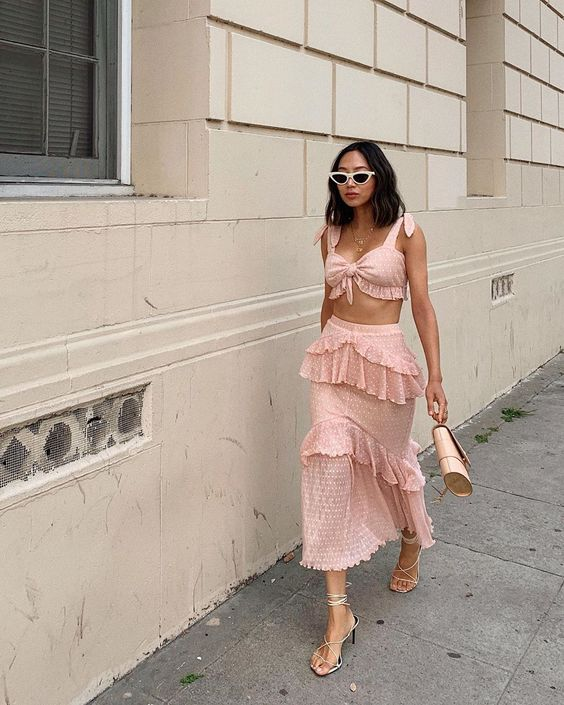 a pink two piece dress with ruffles, a tied up micro top, a ruffle tiered midi skirt and strappy heels for a party