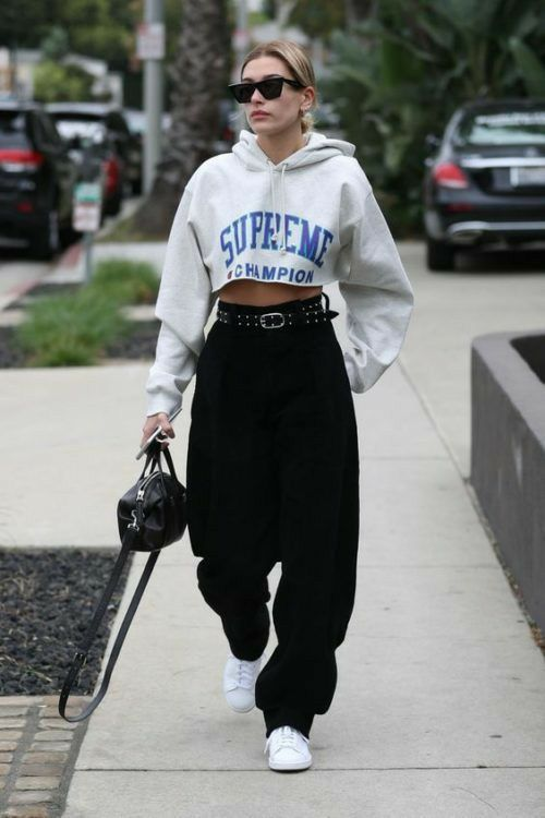 a printed cropped hoodie, black barrel jeans, a belt, a black bag and white sneakers