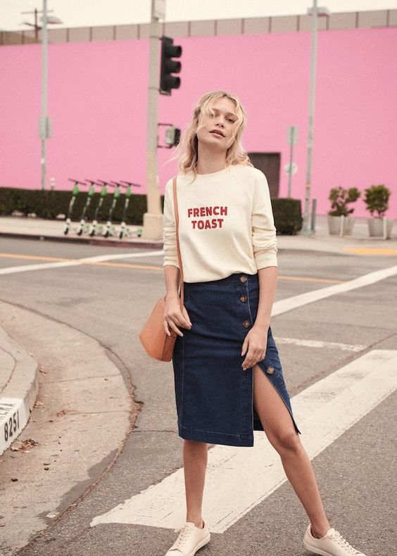 a printed sweatshirt, a blue button up denim midi, white sneakers and an amber leather bag