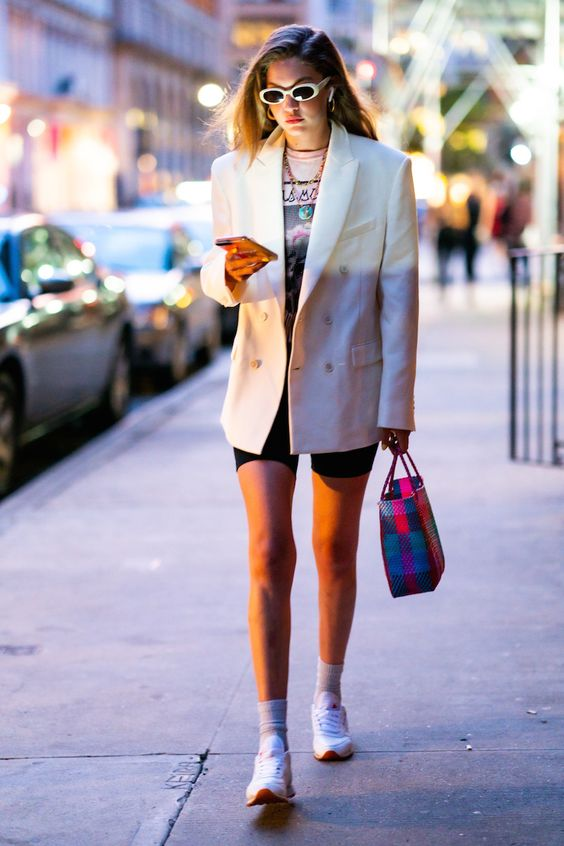 a printed t-shirt, black biker shorts, an oversized white blazer, trainers and socks plus a colorful bag