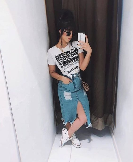 a printed tee, a distressed blue denim midi with a front slit, white sneakers and a printed mini bag