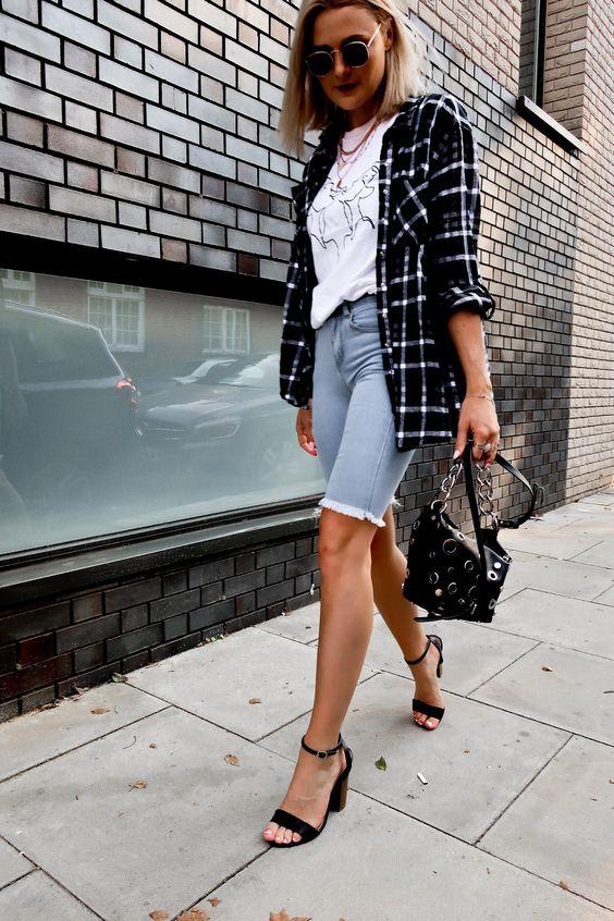 a printed tee, a plaid oversized blazer, blue denim biker shorts, black heels, a black dotted bag