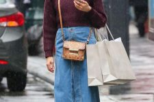 a purple cropped sweater, a blue denim button up midi, mustard booties and a snakeskin print bag