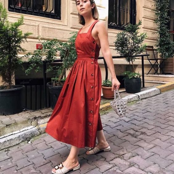 a red line sundress with thick straps, buttons on the side, white mules and a beautiful beaded bag