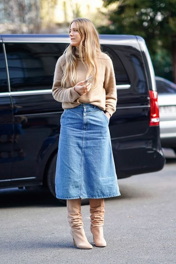 a relaxed and trendy look with a tan jumper, a blue denim midi with pockets, tan boots is simple and chic