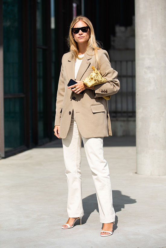 a simple and work-appropriate outfit with a white t-shirt, white jeans, a tan oversized blazer, white heels and a gold bag