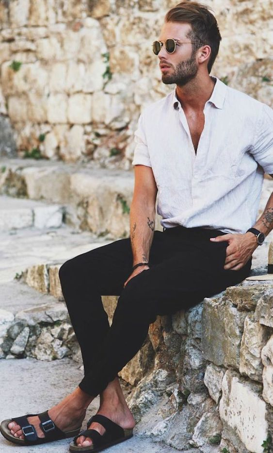 a simple vacation look with a grey linen shirt and black pants plus black slippers and round sunglasses