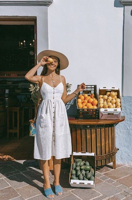 a simple white linen midi sundress on buttons, blue heeled mules, a straw hat and a colorful bag for a cute look