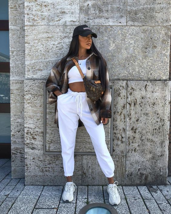 a sport chic look with a white crop top, white sweatpants, trainers, a dark plaid shirt and a baseball cap